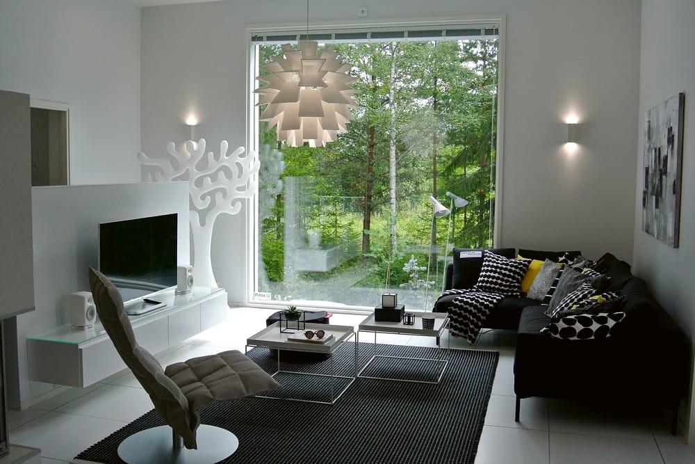 Wohnzimmer in den Farben weiss, grau, schwarz. Blick durch grosses Fenster in grünen Wald
