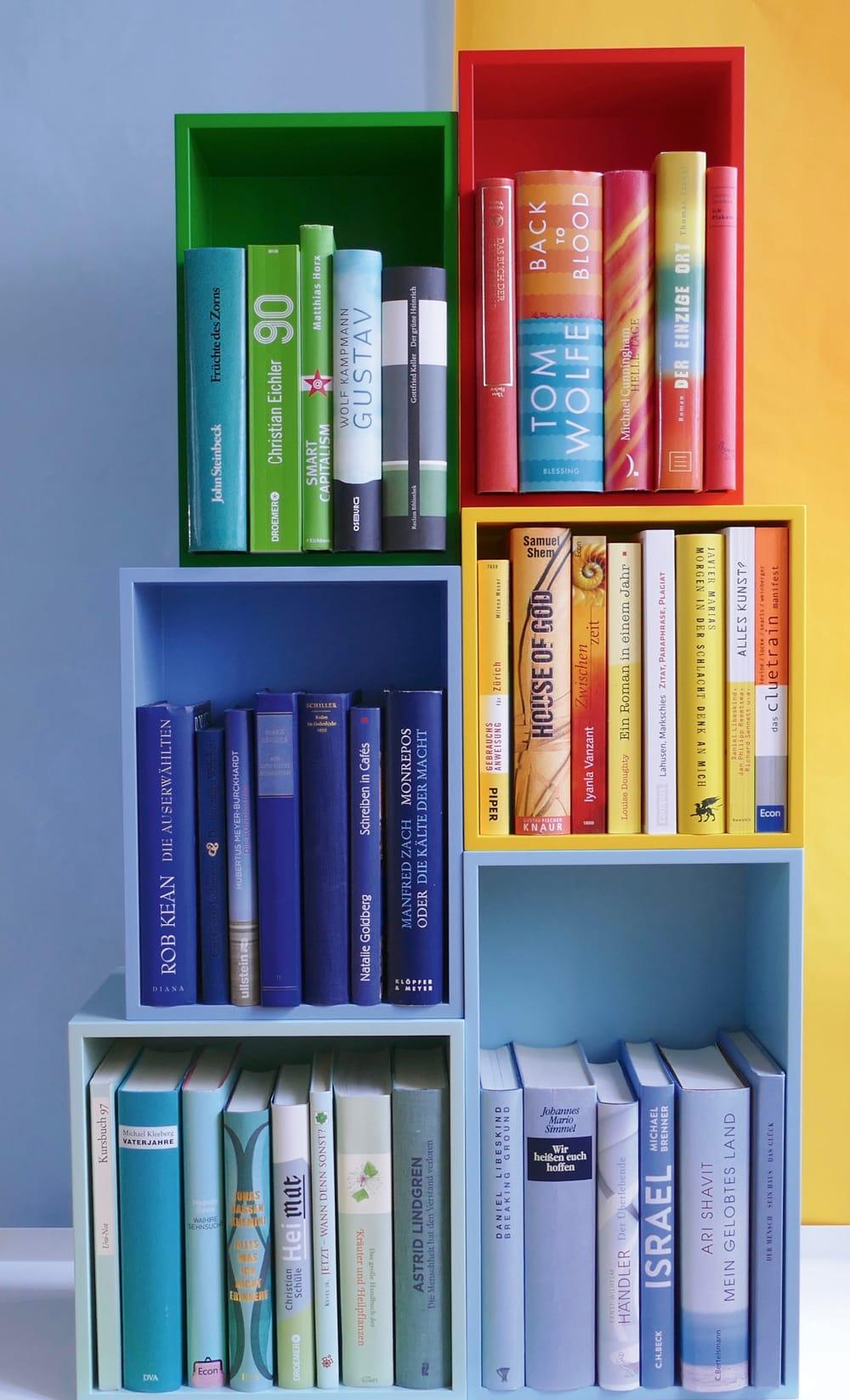 Nach Farben geordnete Bücher in gleichfarbigen Regalen